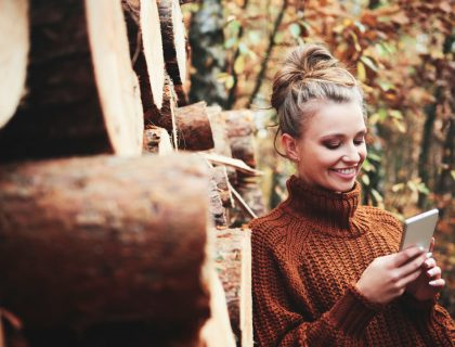 Smiling beautiful woman using digital phone in the autumn forest