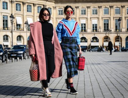 A two girls hold the bags and walking together on road