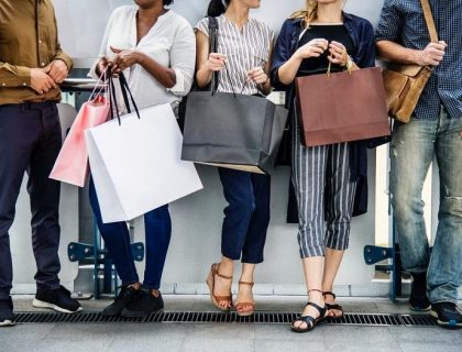 A group of people standing and holding shopping bags